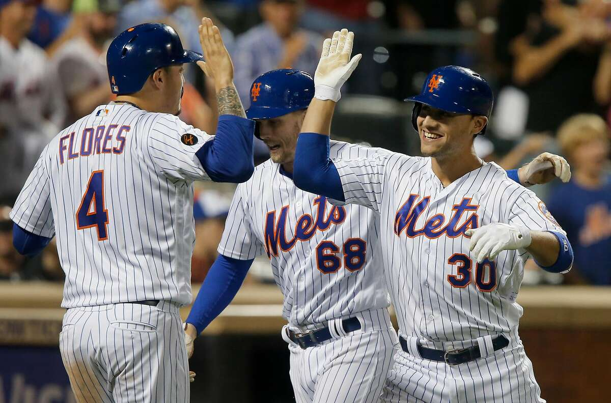 NEW YORK, NY - AUGUST 21: Michael Conforto #30 of the New York Mets celebrates his eighth inning three run home run against the San Francisco Giants with teammates Jeff McNeil #68 and Wilmer Flores #4 at Citi Field on August 21, 2018 in the Flushing neighborhood of the Queens borough of New York City. (Photo by Jim McIsaac/Getty Images)