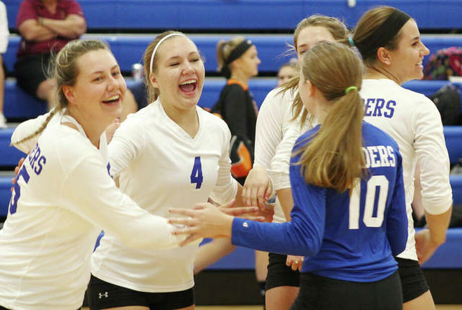 Brussels' Logan Jacobs (left) and Jackie Rose (4) celebrate with teammates after winning set point to rally from a 20-13 deficit to win the second set of their three-set victory over CM on Tuesday at the Roxana Tournament. Photo:     Greg Shashack / The Telegraph
