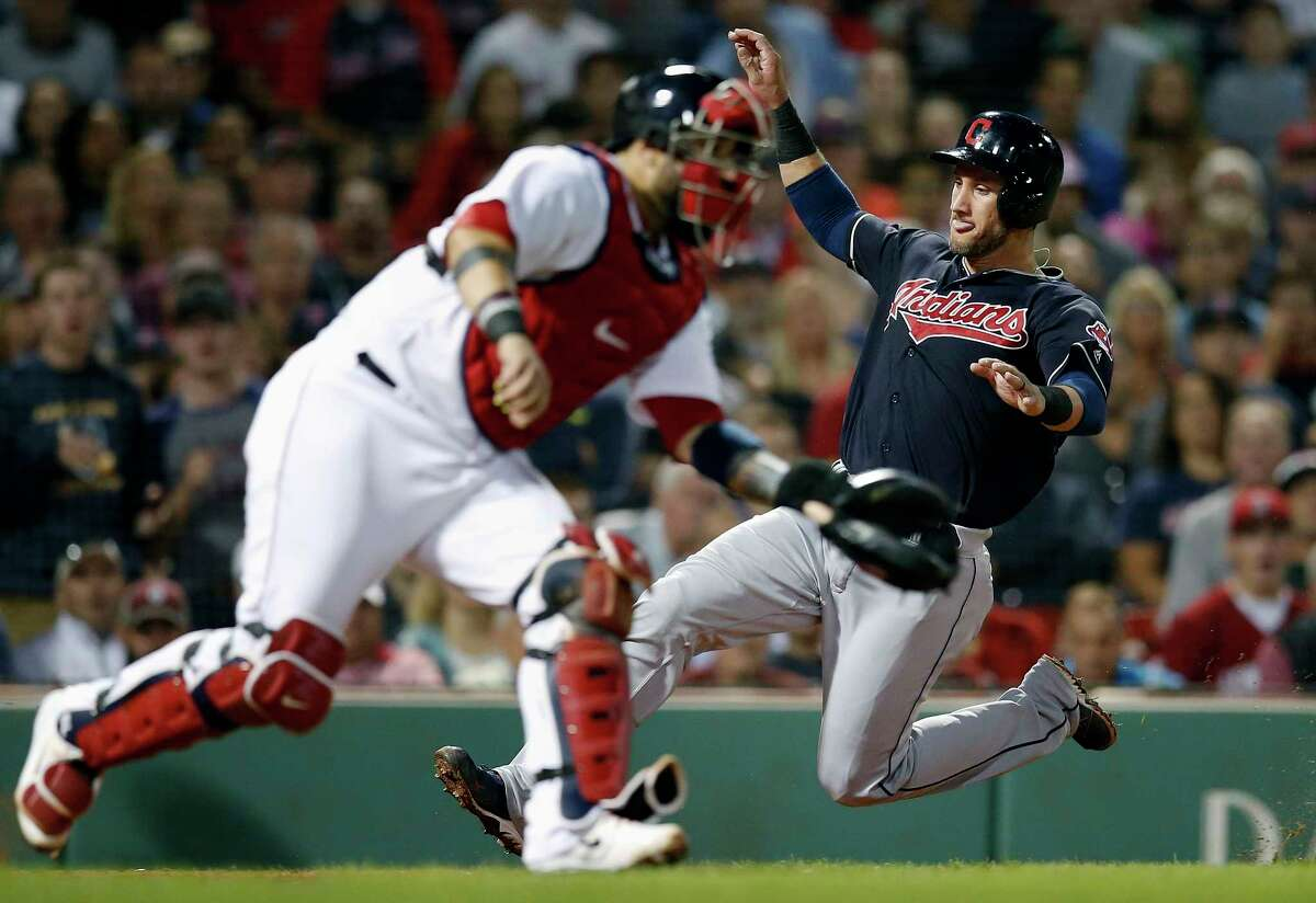 Cleveland Indians' Yan Gomes, right, scores behind Boston Red Sox's Sandy Leon on a single by Michael Brantley during the sixth inning of a baseball game in Boston, Tuesday, Aug. 21, 2018. (AP Photo/Michael Dwyer)