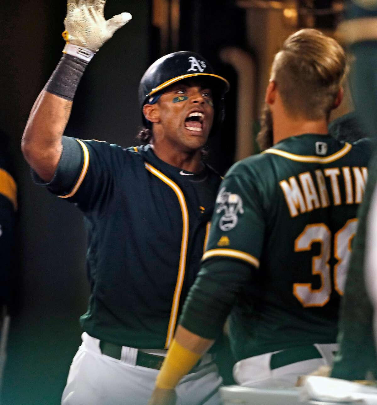 Oakland Athletics' Khris Davis celebrates with Nick Martini after Davis' 2-run home run in 7th inning against Texas Rangers during MLB game at Oakland Coliseum in Oakland, Calif. on Tuesday, August 21, 2018.