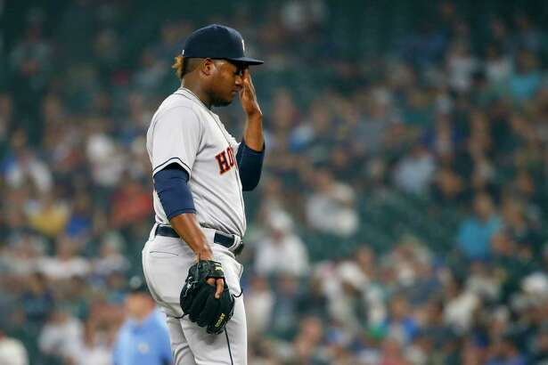 Houston Astros pitcher Framber Valdez wipes his face after hitting Seattle Mariners' Denard Span to load up the bases during the third inning of a baseball game Tuesday, Aug. 21, 2018, in Seattle. (AP Photo/Jennifer Buchanan)