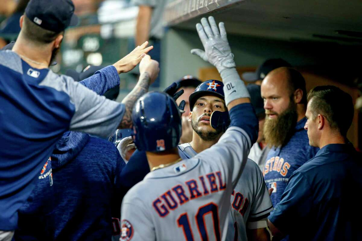 Houston Astros' Carlos Correa is congratulated by teammates in the dugout after hitting a sacrifice fly ball to score Tony Kemp during the third inning of a baseball game against the Seattle Mariners Tuesday, Aug. 21, 2018, in Seattle. (AP Photo/Jennifer Buchanan)