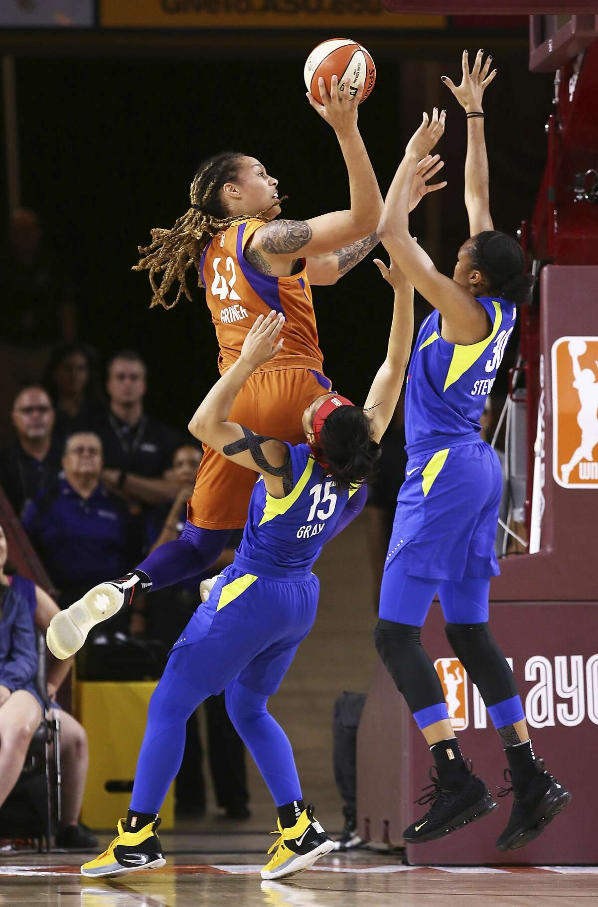 Phoenix Mercury's Brittney Griner (42) puts up a shot over Dallas Wings' Allisha Gray (15) and Azura Stevens (30) in the first half of a first round WNBA basketball playoff game, Tuesday, Aug. 21, 2018, at Wells Fargo Arena, in Tempe, Ariz. Phoenix beat Dallas 101-83. (Rob Schumacher/The Arizona Republic via AP)