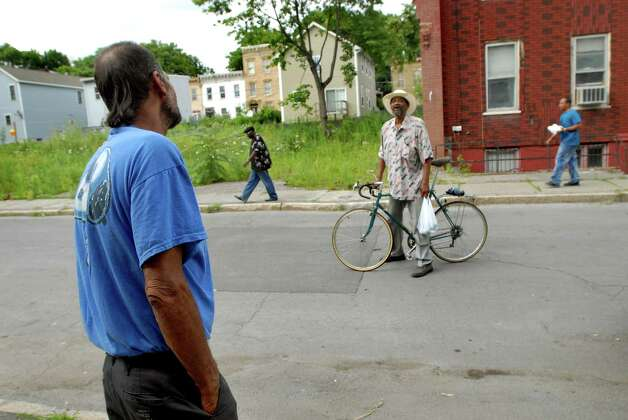 "Samuel ""Poppy"" Baez, left,  stops to talk to man someone traveling through the neighborhood on July 24, 2009, in Albany, N.Y. (Cindy Schultz / Times Union) Photo: CINDY SCHULTZ"