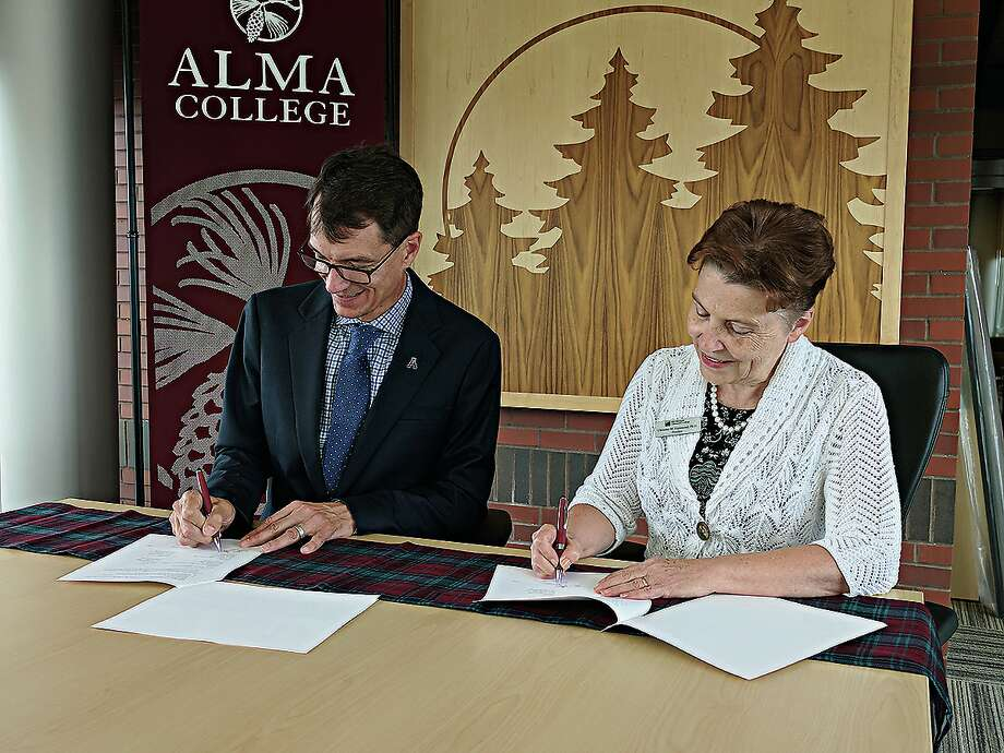 Jeff Abernathy, president of Alma College, and Christine Hammond, president at Mid Michigan College, sign an agreement to provide students with a path to success. (Photo provided) Photo: Photo Provided