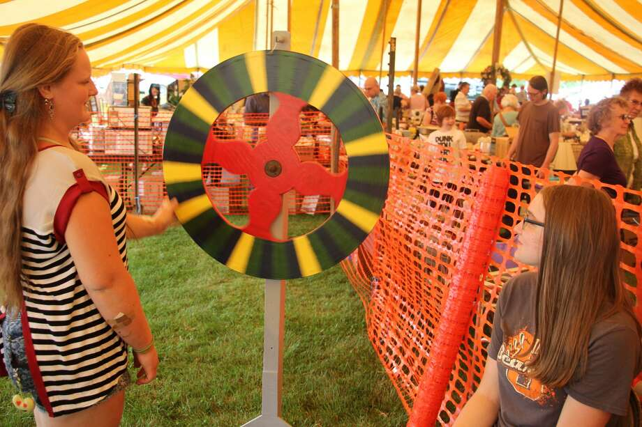 Jacie Tyrrell, 14, of Ubly, spins a game wheel while Lindsey Gosdzinski, 16, of Ubly, looks along, at Sunday's Saint Isidore Summer Festival at Saint Mary Catholic Church in Parisville. Photo: Kate Hessling/Huron Daily Tribune