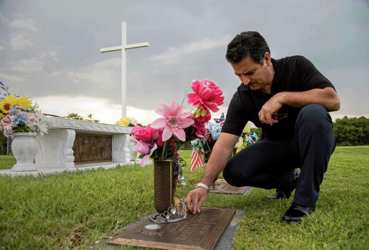 Ric Saldivar cleans the grave of his grand-niece Daisy, while he visits the graves of his parents and their four great-grandchildren, who drowned in a van during Hurricane Harvey, Thursday, Aug. 9, 2018, in Houston.