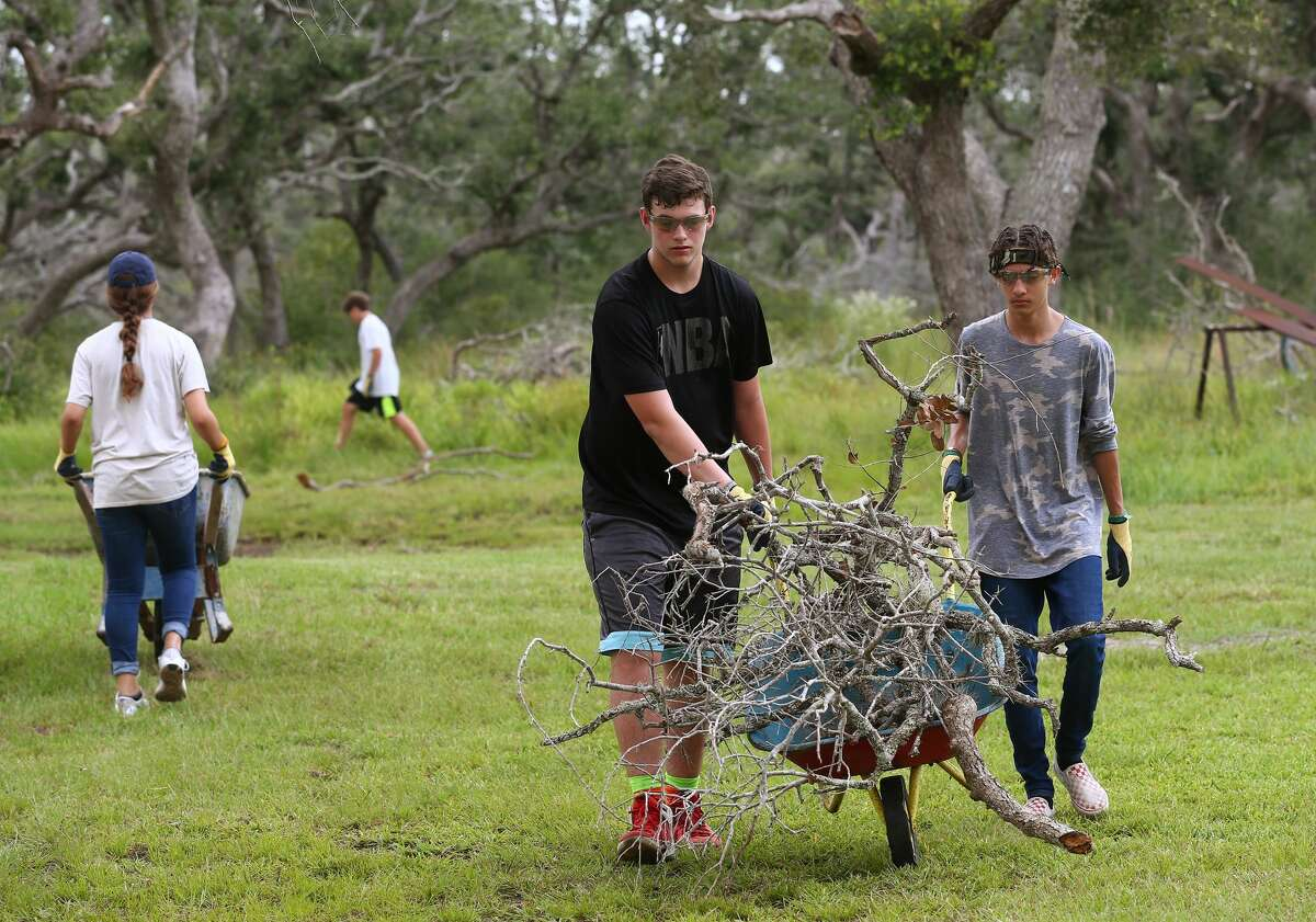 Houston natives Caleb McGrann, 16, center, and Cesar Avila, 15, clear debris from Hurricane Harvey in a Rockport backyard. The teens were volunteering with the Episcopal Diocese of Texas.
