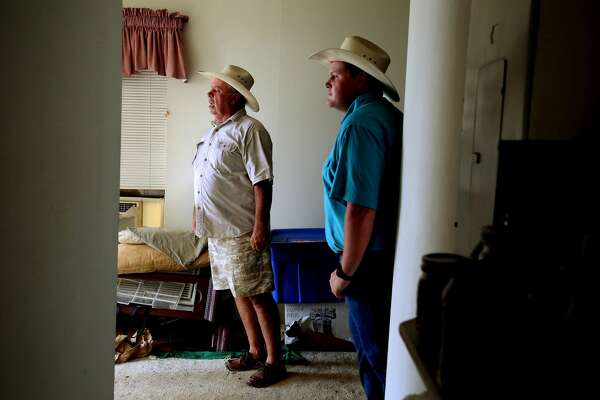Gene Frost, 60, and his son, Hunter, stand inside their Port Aransas home. The storm pushed the structure off its tall poles, leaving it tilted.