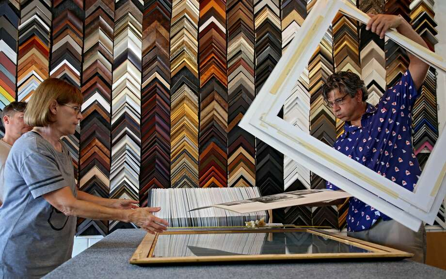 Mike Catlin, who owns Coast Modern, takes apart Michelle Bell's framed lithograph in order to replace the warped mat caused by the storm in Rockport, Texas. (Godofredo A. Vasquez | Houston Chronicle)