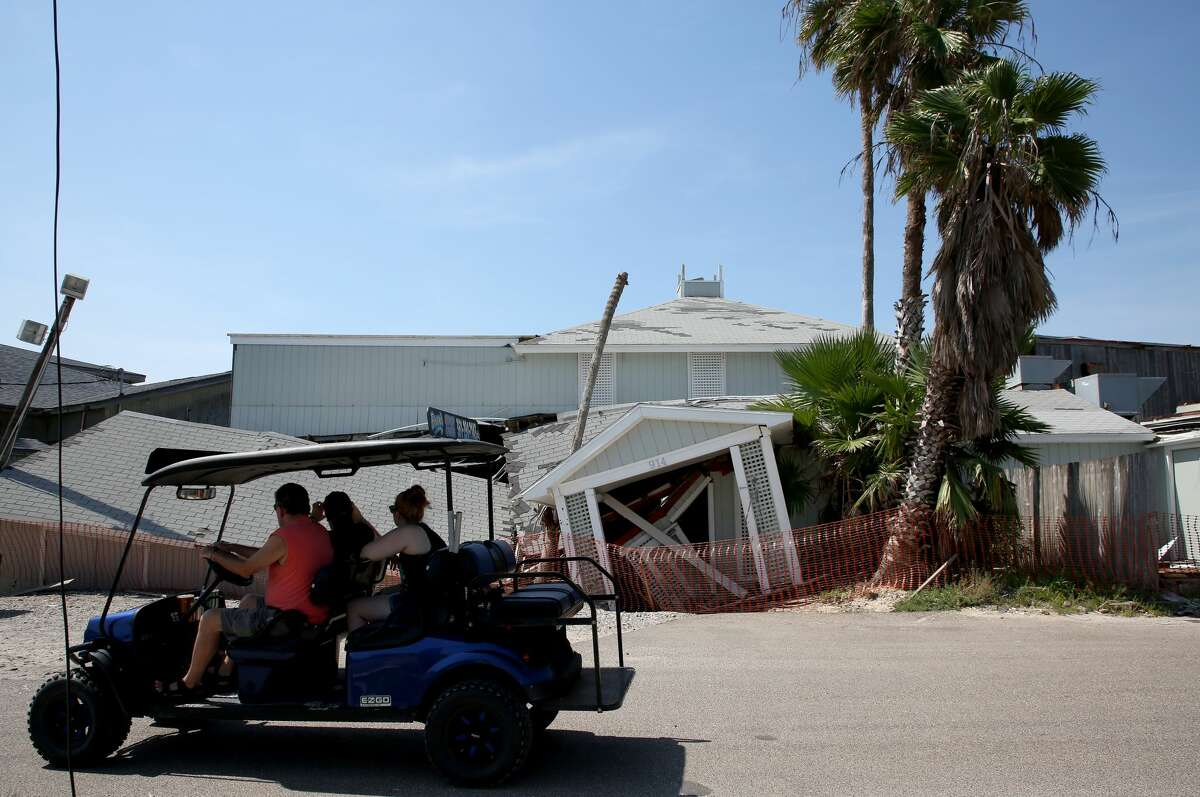 Visitors snap a photo of Pelican Club in Port Aransas. An insurance battle is ongoing over the property.