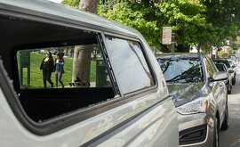 Two women are seen through the broken window of a car parked feet from an auto burglary awareness sign posted near Dolores Park at 18th and Dolores streets Wednesday, April 11, 2018 in San Francisco, Calif.