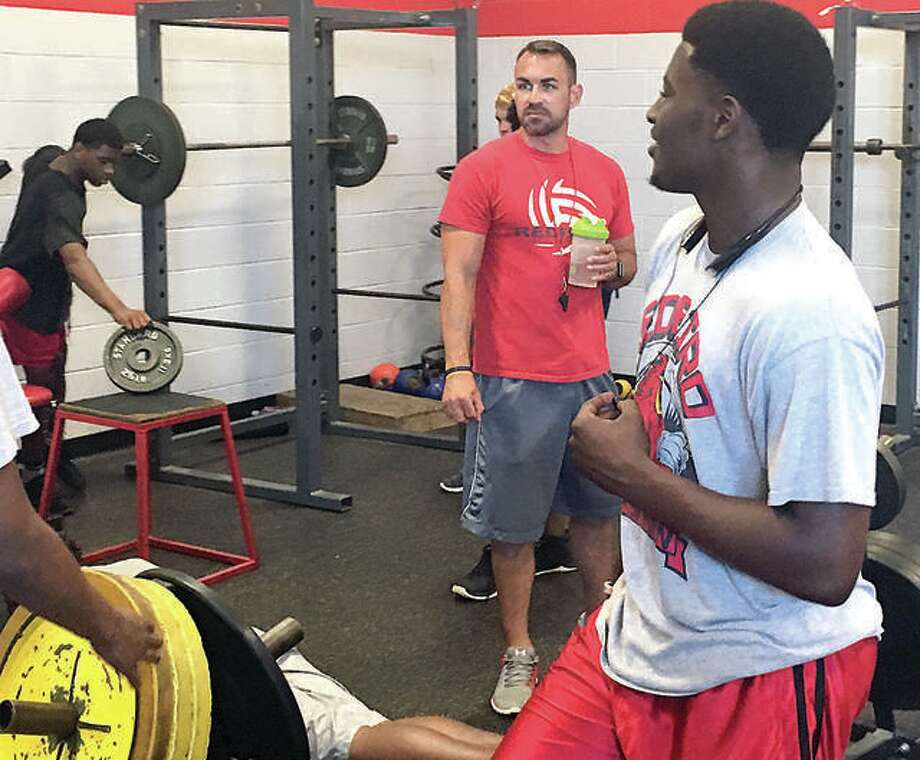 Alton High football coach Eric Dickerson gives advice to players during a summer weight room session at Alton High School. Photo: 