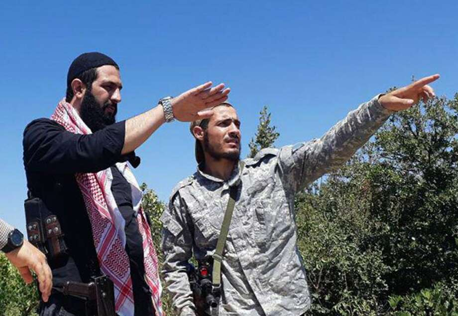 Abu Mohammed al-Golani (left) talks with a fighter of the Levant Liberation Committee as the al Qaeda branch in Syria is known. His forces are facing a possible government offensive. Photo: Associated Press