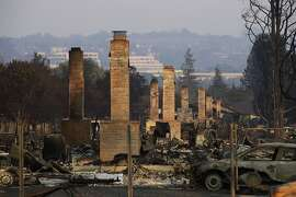 FILE - This Oct. 13, 2017 file photo shows row of chimneys stand in a neighborhood devastated by the Tubbs fire near Santa Rosa, Calif.  In the last year, fires have devastated neighborhoods in the Northern California wine country city of Santa Rosa, the Southern California beach city of Ventura and, now, the inland city of Redding. Hotter weather from changing climates is drying out vegetation, creating more intense fires that spread quickly from rural areas to city subdivisions, climate and fire experts say. But they also blame cities for expanding into previously undeveloped areas susceptible to fire.  (AP Photo/Jae C. Hong, File)