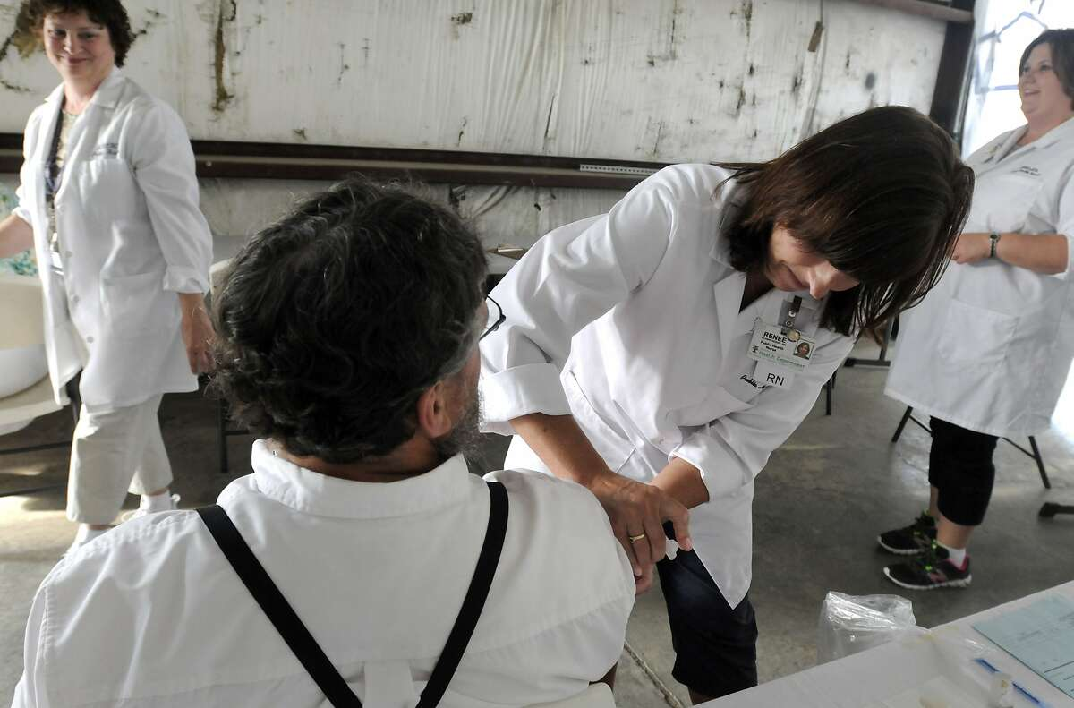 In this June 25, 2014 photo, Richland Public Health nurse Renee Blankenship gives Daniel Martin, an Amish man from Holmes County his Measles, Mumps, & Rubella (MMR) vaccination while he talks with nurses Sue McFarren, left, and Denise Close, right, at a clinic in Shiloh, Ohio. Health officials said Ohio's current outbreak of measles consists of more than 360 cases and is the biggest in the U.S. since 1994. The outbreak started after Amish travelers to the Philippines contracted measles this year and returned home to rural Knox County, Ohio. (AP Photo/Tom E. Puskar)