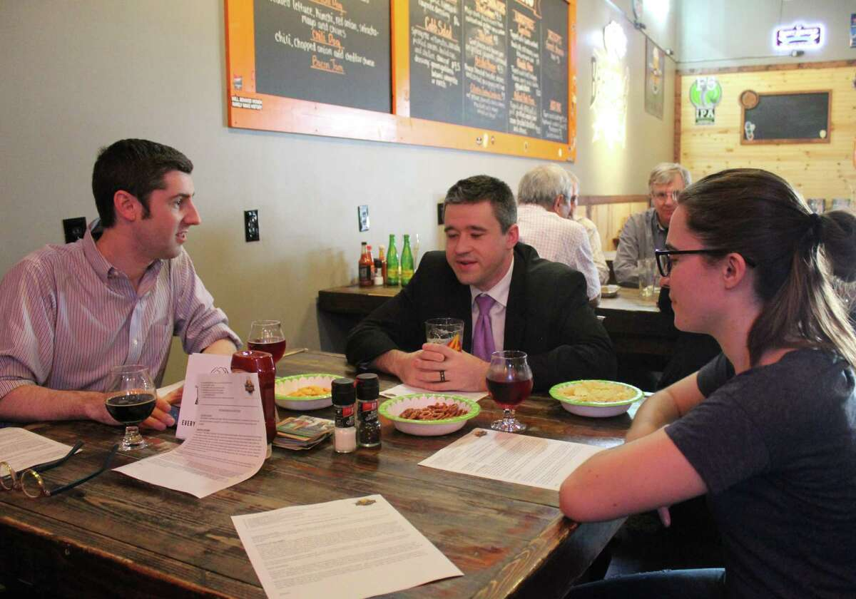 """Mike Mayo, Adam Looney and Josephine Patton gather Tuesday, Aug. 21, at Hop Scholar Ale House for Pub Theology, a weekly meetup group in which attendees discuss a """"Question of the Week"""" regarding theology or philosophy."""
