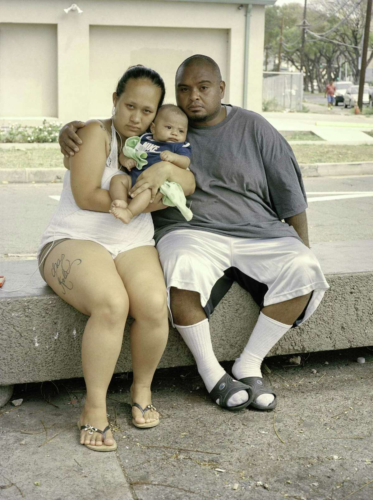 Chas, Kela and baby wait at a bus stop outside Micronesi Mart in Oahu, Hawaii.