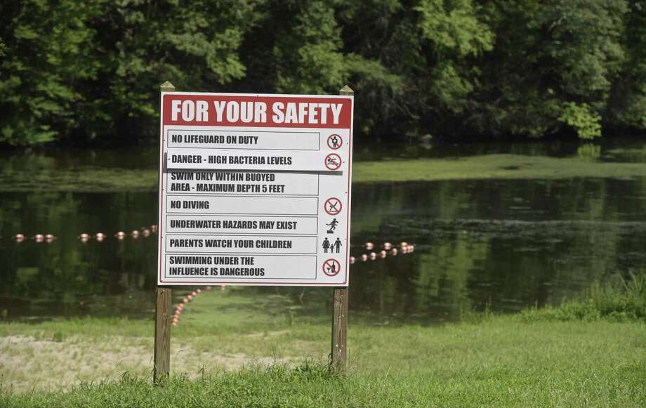 "A sign at the Kettletown State Park beach lists ""High Bacteria Levels"".  Large cyanobacteria blooms in Kettletown State Park has closed the beach. Officials expect the blooms will keep the beach closed for the rest of the season. Thursday, August 9, 2019, in Southbury, Conn. Photo: H John Voorhees III / Hearst Connecticut Media / The News-Times"