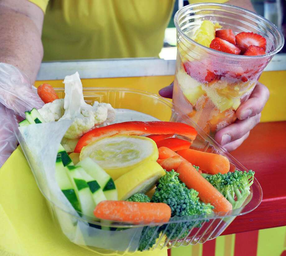 Donna Sharpe of Brett's Fried Food offers up a fresh vegetable platter and fruit cup at the Altamont Fair Tuesday August 14, 2018 in Altamont, NY.  (John Carl D'Annibale/Times Union) Photo: John Carl D'Annibale / 20044532A
