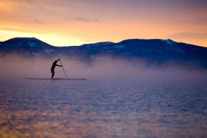 Jake Lamberth paddles through the morning mist above Carnelian Bay.