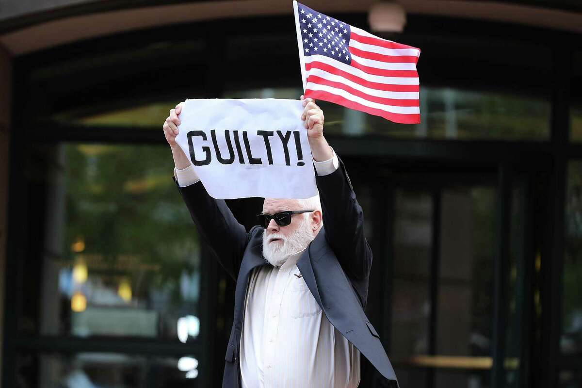 ALEXANDRIA, VA - AUGUST 21: A demonstrator holds up a sign and flag after leaving the Albert V. Bryan U.S. Courthouse after the jury announced verdicts in the trial for former Trump campaign manager Paul Manafort's trial August 21, 2018 in Alexandria, Virginia. Manafort was found guilty on at least one count as part of special counsel Robert Mueller's investigation into Russian interference in the 2016 presidential election. (Photo by Chip Somodevilla/Getty Images) *** BESTPIX ***