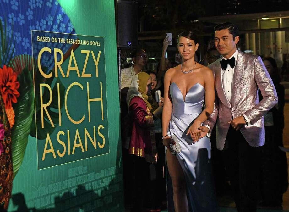 """Actor Henry Golding, right, and his wife Liv Lo arrive at the film premiere of """"Crazy Rich Asians"""" at the Capitol Theatre in Singapore on Tuesday. Photo: ROSLAN RAHMAN /AFP /Getty Images / AFP or licensors"""