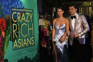 """Actor Henry Golding, right, and his wife Liv Lo arrive at the film premiere of """"Crazy Rich Asians"""" at the Capitol Theatre in Singapore on Tuesday."""