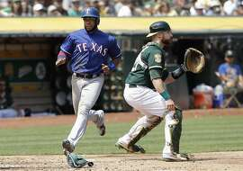 Texas Rangers' Elvis Andrus, left, scores a run against Oakland Athletics catcher Jonathan Lucroy during the fifth inning of a baseball game in Oakland, Calif., Wednesday, Aug. 22, 2018. (AP Photo/Jeff Chiu)