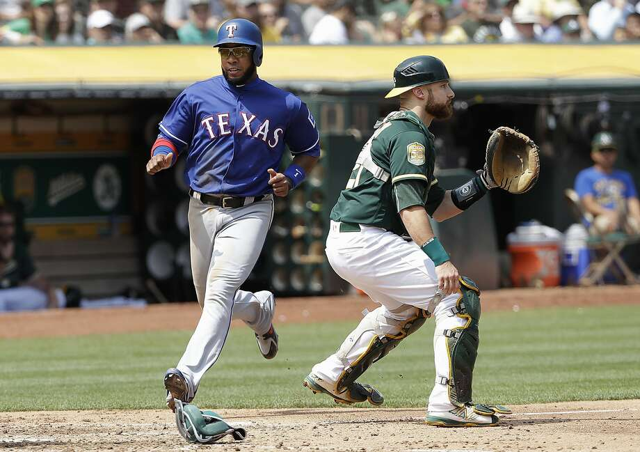 Texas' Elvis Andrus scores his team's final run in the fifth inning as A's catcher Jonathan Lucroy awaits the throw to the plate. Photo: Jeff Chiu / Associated Press