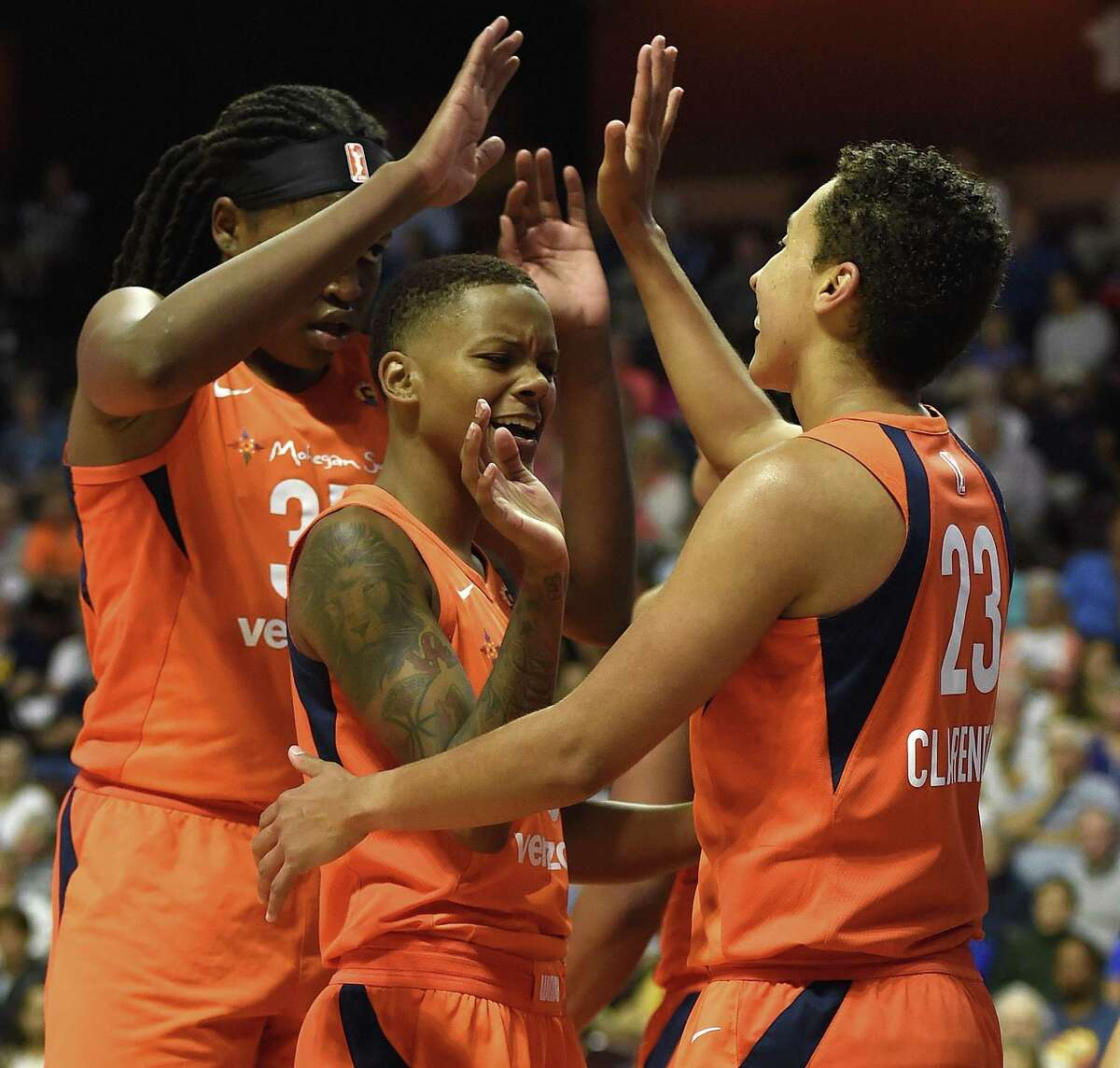 Connecticut Sun center Jonquel Jones, left, and guard Courtney Williams congratulate Layshia Clarendon after she scored and was fouled on a play against the Minnesota Lynx during the second half of on Aug. 17.
