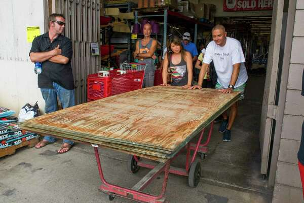 In this photo taken Tuesday, Aug. 21, 2018, Jodi Nishida and Sam Delovio push along plyboard they purchased at a City Mill store before the arrival of a hurricane in Honolulu. Hurricane Lane has weakened as it approaches Hawaii but was still expected to pack a wallop, forecasters said Wednesday, as people hurried to buy water and other supplies and the Navy moved its ships to safety. (Craig T. Kojima/Honolulu Star-Advertiser via AP)