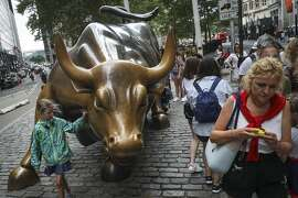 NEW YORK, NY - AUGUST 22: Tourists visit the Wall Street bull statue in the Financial District, August 22, 2018 in New York City. Today marks the longest bull market rally in U.S. history, stretching back to March 2009. The longest previous market rally was from 1990 to March 2000. (Photo by Drew Angerer/Getty Images)