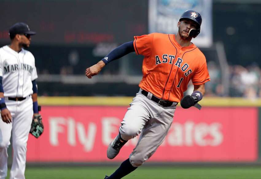 Houston Astros' Carlos Correa (1) races past Seattle Mariners third baseman Robinson Cano to score in the first inning of a baseball game Wednesday, Aug. 22, 2018, in Seattle. (AP Photo/Elaine Thompson)