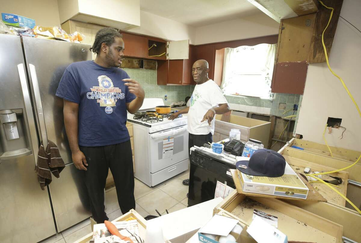 Jahvuon King-Registe, a University of Houston student, left, talks to his grandfather, Albert King, in the family's home that flood during Hurricane Harvey shown Tuesday, Nov. 14, 2017, in Pearland.(Melissa Phillip | Houston Chronicle)