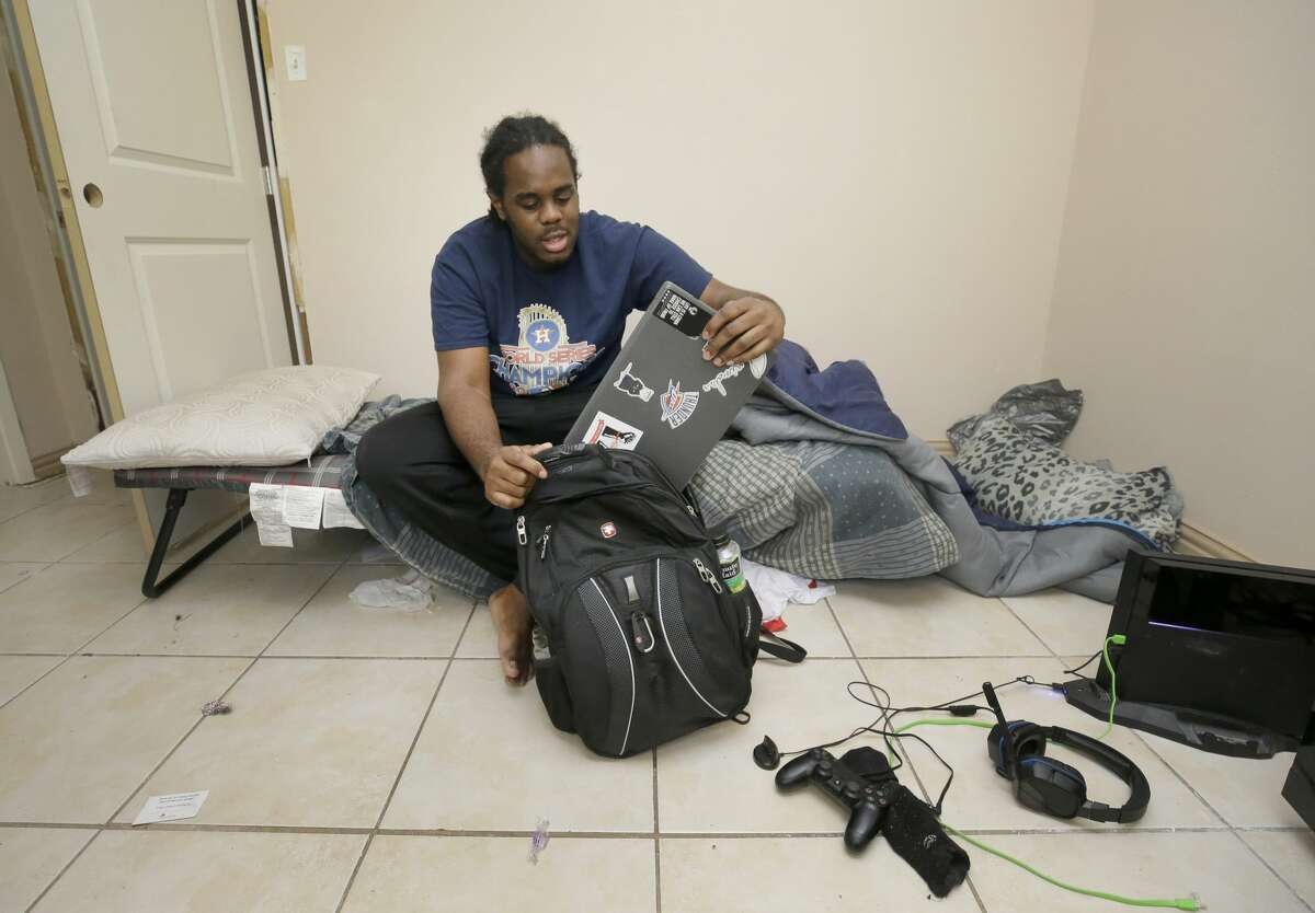 Jahvuon King-Registe, a University of Houston student, takes out the computer he uses for his school work as he sits on his cot in his room at his family's home that flood during Hurricane Harvey shown Tuesday, Nov. 14, 2017, in Pearland.