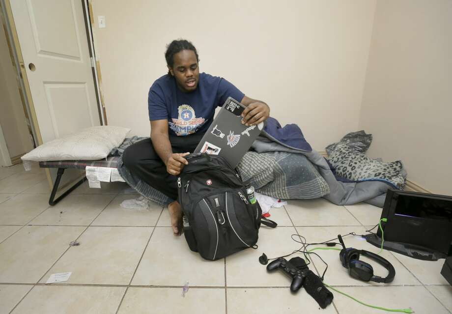 Jahvuon King-Registe, a University of Houston student, takes out the computer he uses for his school work as he sits on his cot in his room at his family's home that flood during Hurricane Harvey shown Tuesday, Nov. 14, 2017, in Pearland. Photo: Melissa Phillip