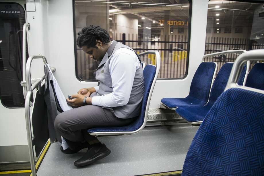 Jahvuon King-Registe checks his phone as he rides the Light Rail on his way to his home near midnight, Wednesday, June 13, 2018, in Houston. (Marie D. De Jesus| Houston Chronicle)