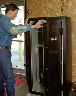 Johnny Dury of Dury's Gun Shop checks out the interior of a Granite Security gun safe on display in his shop. photo by Ralph Winingham