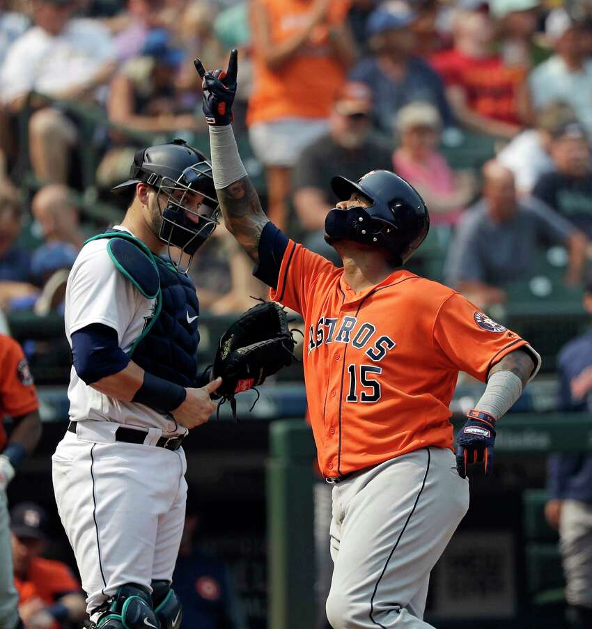 Houston Astros' Martin Maldonado, right, points to the sky as he crosses home in front of Seattle Mariners catcher Mike Zunino after his solo home run in the fifth inning of a baseball game Wednesday, Aug. 22, 2018, in Seattle. (AP Photo/Elaine Thompson)