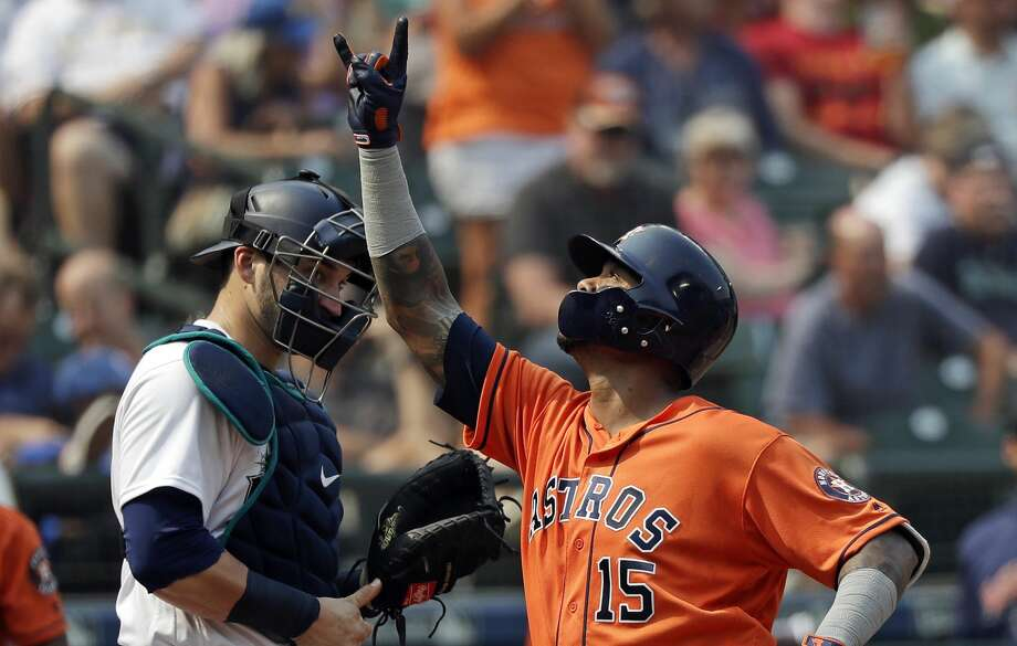 Houston Astros' Martin Maldonado, right, points to the sky as he crosses home in front of Seattle Mariners catcher Mike Zunino after his solo home run in the fifth inning of a baseball game Wednesday, Aug. 22, 2018, in Seattle. (AP Photo/Elaine Thompson) Photo: Elaine Thompson/AP
