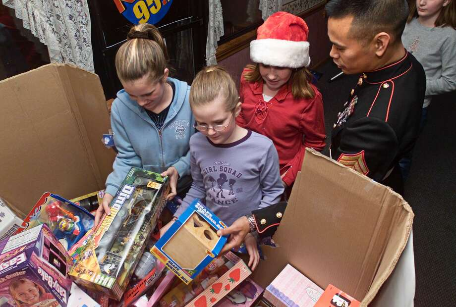 Marine Gunnery Sgt. Norman Agustin looks over some of the donated toys along with some helpers at a party at Brothers Restaurant in Wallingford. The kids are: Left to Right: Nikki Soderlund (11), Macaire Chasse (10) and Colleen Marquis (10), all of Wallingford. The toys will go to the Toys For Tots campaign. Photo: Peter Casolino / ©Peter Casolino File Photo