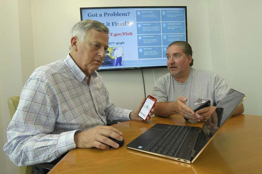 Stamford city representatives Bob Lion and Eric Morson, photograph on August 22, 2018, collaborate on a power point presentation that is airing on Optimum's Government Cable TV Access Channel 79. in Stamford, Connecticut on August 22, 2018. Lions plans to add video and all kinds of stuff, giving residents info about the city. The city has had access to this channel, allowed under Area Nine Cable Council rules, for this purpose for many years but never took advantage of it, as other cities do. Photo: Matthew Brown / Hearst Connecticut Media / Stamford Advocate