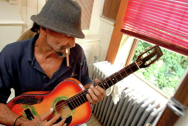 "Samuel ""Poppy"" Baez strums a guitar that has only two strings on Tuesday, Aug. 11, 2009, at his apartment in Albany, N.Y. (Cindy Schultz / Times Union) Photo: CINDY SCHULTZ"