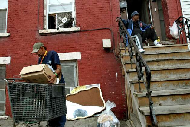 "Samuel ""Poppy"" Baez, left, moves his belongings from a shopping cart into a filthy basement apartment on Tuesday, Sept. 8, 2009, on Grand Street in Albany, N.Y. He said he moved here because the rent's less expensive. (Cindy Schultz / Times Union) Photo: CINDY SCHULTZ"