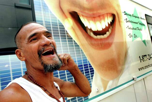 "Samuel ""Poppy"" Baez shows off his new teeth outside the American Mobile Dental office on Monday, Aug. 24, 2009, on Pearl Street in Albany, N.Y. Poppy got a set of dentures after losing his real teeth in a street fight. (Cindy Schultz / Times Union) Photo: CINDY SCHULTZ"