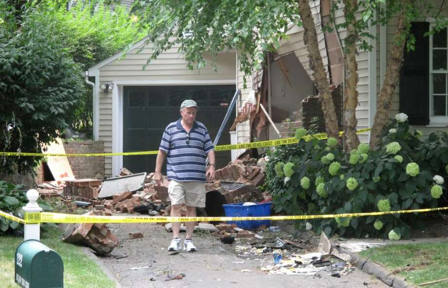 A man inspects damange after a Darien resident was killed when he drove his car through an unoccupied bedroom of a home, hit a tree and into another house on Hollow Tree Ridge Road in Darien at approximately 1:30 a.m. on Sunday, July 11, 2010. Photo: Chris Preovolos / Stamford Advocate