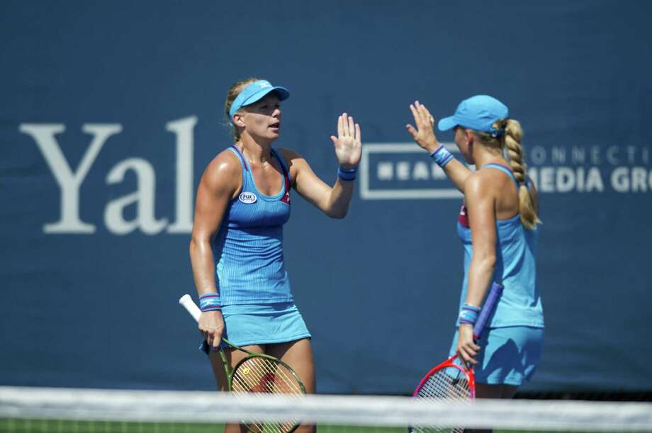 Partners Kiki Bertens, left, and Johanna Larsson high-five after winning a point during a first round doubles match against Monique Adamczak and Oksana Kalashnikova at the Connecticut Open in New Haven Wednesday. Bertens and Larsson won 6-3, 6-4. Photo: Michael Cummo / Hearst Connecticut Media / Stamford Advocate