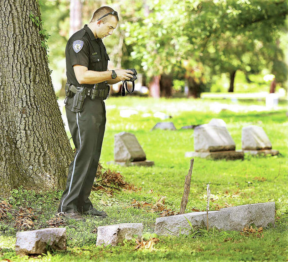 An Alton Police officer photographs the headstone where some unusual items were found Wednesday by a grounds crew at the Upper Alton Cemetery on Oakwood Rd. The workers recovered a cash register and a cash drawer, found about 50 feet apart. The register was left on a grave marker, and the drawer was found on a stone, perimeter enclosure of a family grave plot. There was no cash in sight. Photo: John Badman | The Telegraph