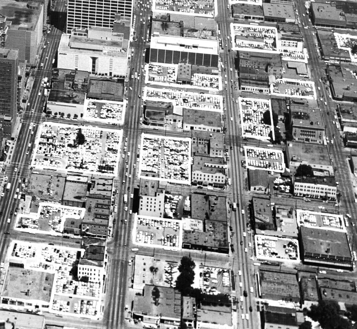 May 1961: Aerial view of downtown Houston shows location of parking lots in white boxes. Downtown Houston liberally sprinkled with parking lots. Estimated value of land occupied by lots is in excess of $30 million (in 1961 dollars). Sakowitz can be seen in the upper left.